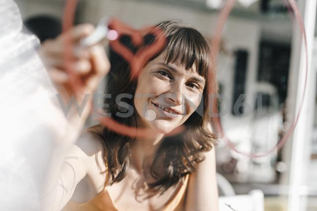 Woman sitting in cafe drawing heart shape on window pane with lipstick - KNSF01941 - Kniel Synnatzschke/Westend61