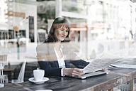 Businesswoman sitting cafe, reading newspaper - KNSF01959