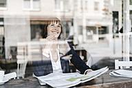 Businesswoman sitting cafe, reading newspaper - KNSF01962