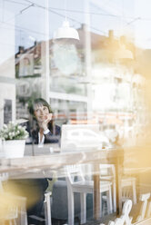 Businesswoman sitting in cafe with laptop, smiling and thinking - KNSF01968