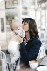 Businesswoman in cafe kissing her baby - KNSF01974