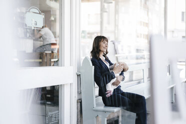Businesswoman in cafe holding sleeping baby - KNSF01977