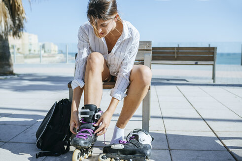 Young woman putting on inline skates - KIJF01633