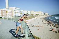 Young woman on inline skates looking at the beach - KIJF01642