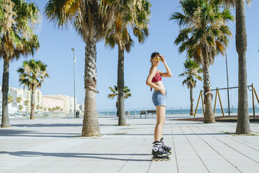 Young woman on inline skates on boardwalk with palm trees - KIJF01645