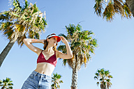 Portrait of young woman with bikini and sun visor with blue sky background and palm trees - KIJF01654