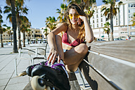 Young woman with inline skates wearing sunglasses sitting on a bench - KIJF01657