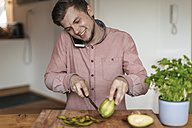 Smiling man on the phone chopping acocado in the kitchen - GUSF00063