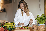 Smiling woman on the phone chopping vegetables in the kitchen - GUSF00066
