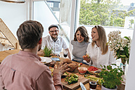 Man telling stories while preparing food with his friends - GUSF00093