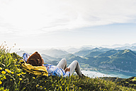 Austria, Salzkammergut, Hiker taking a break, looking over the Alps - UUF10989