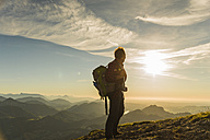 Austria, Salzkammergut, Hiker standing on summit, looking at view - UUF11004
