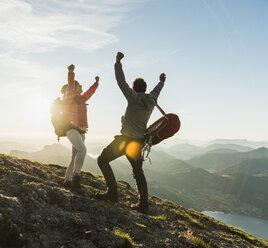 Austria, Salzkammergut, Cheering couple reaching mountain summit - UUF11025