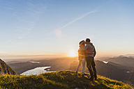 Austria, Salzkammergut, Couple standing on mountain summit, enjoying the view - UUF11046