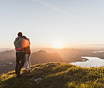 Austria, Salzkammergut, Couple standing on mountain summit, enjoying the view - UUF11049
