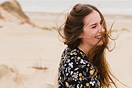Portrait of laughing woman with blowing hair on the beach - NMSF00124