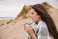 Young woman with cup of hot chocolate on the beach - NMSF00127
