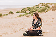 Pensive young woman sitting on the beach with a book - NMSF00130