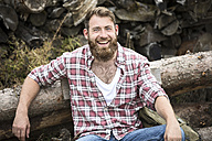 Portrait of laughing bearded man sitting on stack of wood - MAEF12380