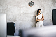 Businesswoman standing under wall clock with arms crossed - KNSF01996