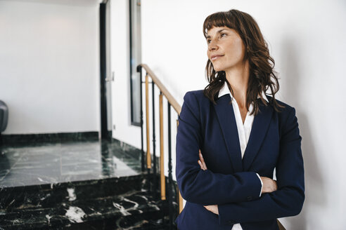 Successful businesswoman standing on staircase - KNSF02011