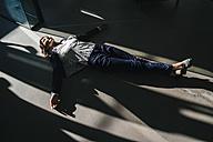 Businesswoman lying on floor in office - KNSF02032