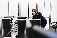 Successful businesswoman looking at monitors in office - KNSF02038
