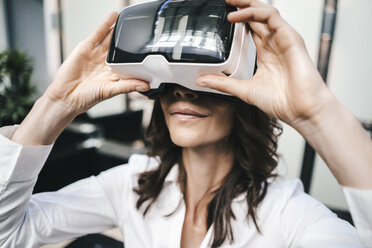 Businesswoman using VR goggles in office - KNSF02041