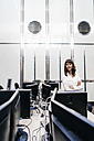 Successful businesswoman standing in office, looking at camera - KNSF02044