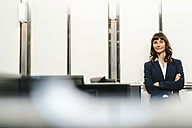 Successful businesswoman standing in office with arms crossed - KNSF02047