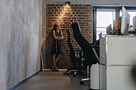 Businesswoman standing in office with arms crossed, looking at lamp - KNSF02059