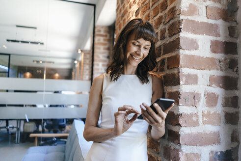 Businesswoman standing in office, holding smartphone - KNSF02077