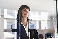 Successful businesswoman looking through glass pane - KNSF02104