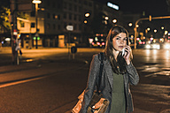 Portrait of young businesswoman with leather bag on the phone at night - UUF11055