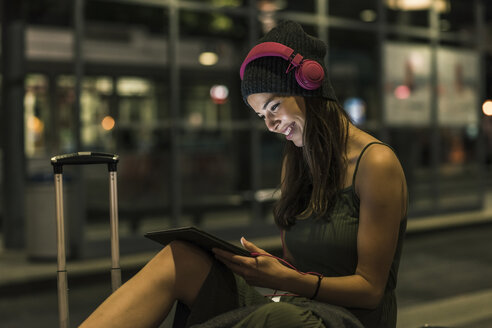 Smiling young woman with headphones and tablet waiting at station by night - UUF11067