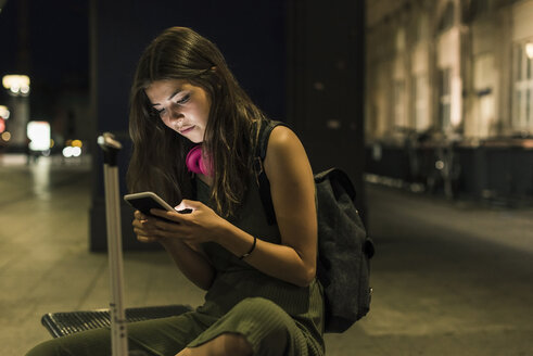 Young woman with backpack and baggage using cell phone at night - UUF11070