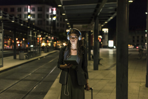 Portrait of young woman with headphones and tablet waiting at station by night - UUF11073