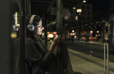 Young woman with headphones waiting at the station by night using tablet - UUF11076