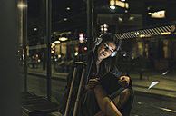 Portrait of young woman with headphones and tablet waiting at station by night - UUF11079