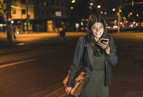 Laughing young businesswoman with leather bag on the phone at night - UUF11082