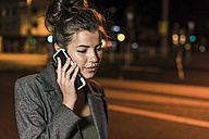Young woman on the phone at night - UUF11085