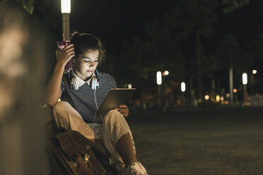 Young woman with smoothie sitting on bench at night using tablet - UUF11088