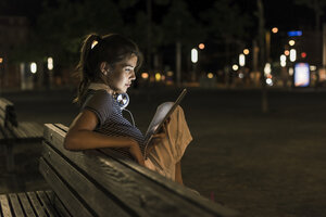 Young woman sitting on bench at night using tablet - UUF11091