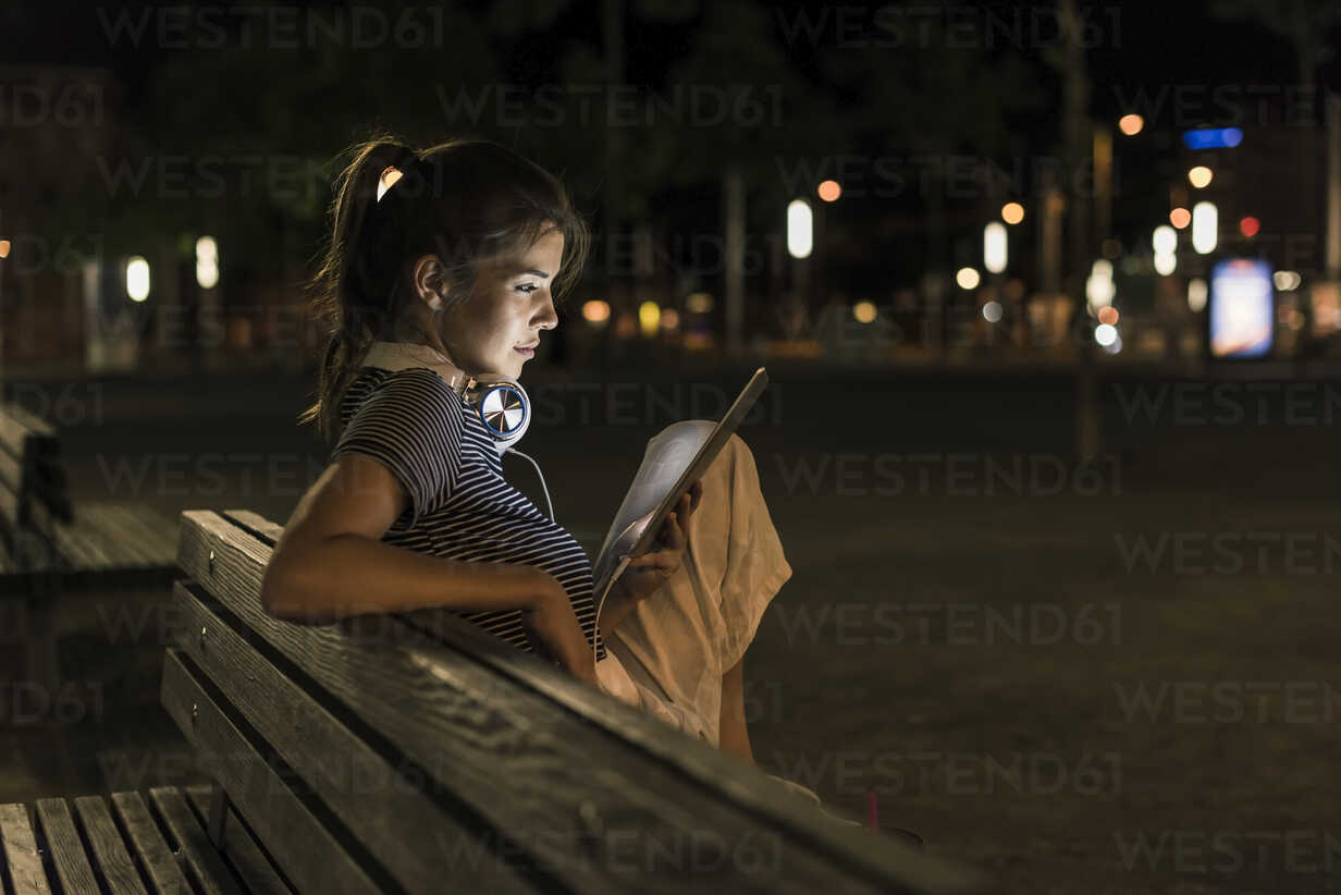 Young woman sitting on bench at night using tablet - UUF11091 - Uwe Umstätter/Westend61