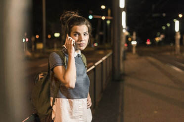 Portrait of young woman on the phone waiting at station by night - UUF11094