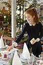 Teenage girl setting the table for Christmas dinner - LBF01624