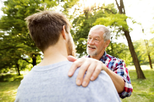 Happy senior father and his adult son in a park - HAPF01863