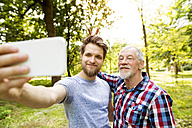 Portrait of senior father and his adult son taking selfie in a park - HAPF01866