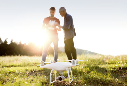 Senior father and his adult son with drone on a meadow - HAPF01869