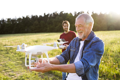 Senior father and his adult son with drone on a meadow - HAPF01872